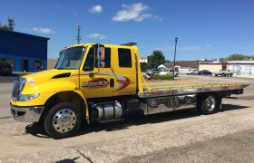 Bock's Service yellow flat-bed hauling truck