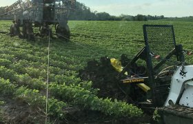 Portable winch machine being used to pull farm equipment from a field